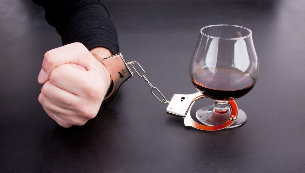 Алкоголизм, рука в наручниках и бокал с коньяком