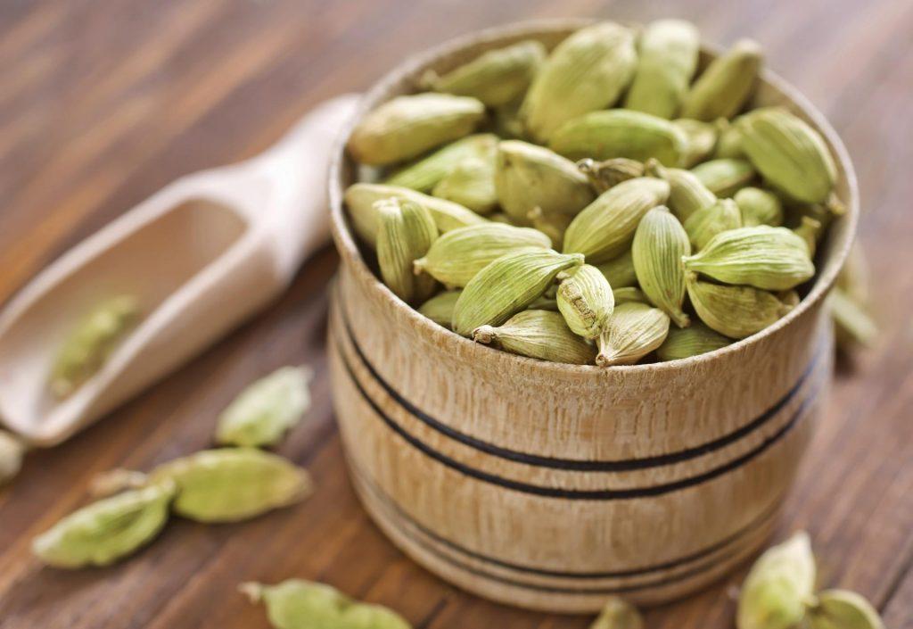 Семена кардамона в деревянной миске и лопатка