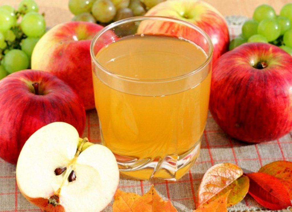Яблочный сок в стеклянном стакане и яблоки